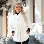 Young blond woman wearing white warm coat walking on city street in autumn. Fall casual fashion, elegant everyday look. Plus size model.
